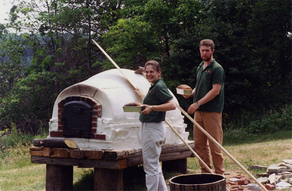 Staff baking bread with the bread oven in 1999. They baked bread once a week and gave it to museum visitors